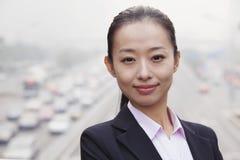 Retrato da mulher de negócios nova Looking na câmera com tráfego abaixo Imagens de Stock Royalty Free