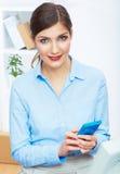 Retrato da mulher de negócios nova no escritório no telefone. Fotografia de Stock