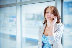 Retrato da mulher de negócios nova que fala no telefone celular no corredor do escritório Foto de Stock Royalty Free