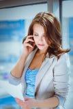 Retrato da mulher de negócios nova que fala no telefone celular no corredor do escritório Fotos de Stock Royalty Free
