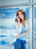 Retrato da mulher de negócios nova que fala no telefone celular no corredor do escritório Imagem de Stock