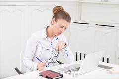 Retrato da mulher de negócios preocupada na mesa no escritório fotografia de stock