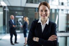 Retrato da mulher de negócios que está com os braços cruzados Imagem de Stock