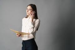 Retrato da mulher de negócios que fala no telefone Um é isolado em um fundo cinzento Imagens de Stock