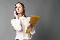 Retrato da mulher de negócios que fala no telefone Um é isolado em um fundo cinzento Fotos de Stock