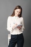 Retrato da mulher de negócios que guarda um caderno e uma pena em sua mão Um é isolado em um fundo cinzento Imagem de Stock Royalty Free