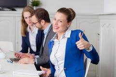 Retrato da mulher de negócios que mostra os polegares acima durante o negócio imagens de stock