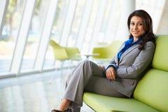 Retrato da mulher de negócios que senta-se no sofá no escritório moderno Imagens de Stock Royalty Free