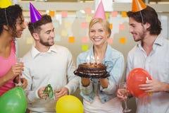 Retrato da mulher de negócios feliz que guarda o bolo de aniversário Imagem de Stock