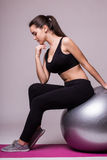 Retrato da mulher de pensamento que senta-se na bola dos pilates Fotos de Stock