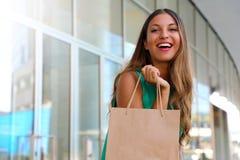 Retrato da mulher de riso atrativa com o saco do cliente em sua mão com alargamento Menina de sorriso da forma da beleza que faz  fotos de stock
