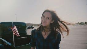 Retrato da mulher de sorriso bonita nova com o cabelo que funde no vento que levanta no parque de estacionamento perto do movimen video estoque
