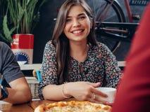 Retrato da mulher de sorriso bonita nova que olha a câmera que senta-se no café bebendo do restaurante e que come a pizza com Foto de Stock