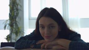Retrato da mulher de sorriso bonita que inclina-se no sofá filme