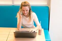 Retrato da mulher de sorriso bonita que senta-se em uma cadeira confortável em um café com portátil preto Estudante bonito que fa Imagens de Stock