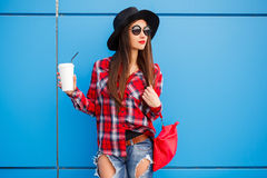 Retrato da mulher de sorriso da forma da beleza com café nos óculos de sol no fundo azul outdoor Cópia-espaço Saco vermelho fotografia de stock royalty free