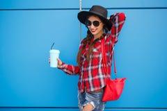 Retrato da mulher de sorriso da forma da beleza com café nos óculos de sol no fundo azul outdoor Copyspace fotografia de stock