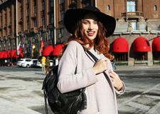Retrato da mulher de sorriso feliz bonita de Yong que veste o chapéu à moda, revestimento Passeio modelo na rua da cidade europei foto de stock