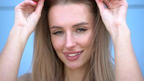 Retrato da mulher de sorriso da forma da beleza com penteado do voo, em óculos de sol de néon cor-de-rosa no fundo azul ocasional video estoque