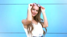 Retrato da mulher de sorriso da forma da beleza com penteado do voo, em óculos de sol de néon cor-de-rosa no fundo azul ocasional filme