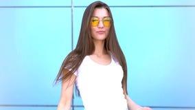 Retrato da mulher de sorriso da forma da beleza com penteado do voo, em óculos de sol de néon cor-de-rosa no fundo azul ocasional vídeos de arquivo