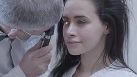 Retrato da mulher de sorriso moreno bonita que senta-se na cadeira do oculista do doutor que faz o profissional do teste do olho filme