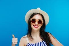 Retrato da mulher de sorriso no chapéu e nos óculos de sol do verão que mostram os polegares acima no fundo azul no estúdio fotografia de stock royalty free