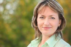 Retrato da mulher de sorriso no parque adiantado da queda fotografia de stock