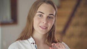 Retrato da mulher de sorriso nova bonita despreocupada segura com os olhos coloridos diferentes que olham a câmera dentro filme