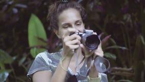 Retrato da mulher de sorriso nova com o cabelo encaracolado que guarda a câmera e que toma fotos filme