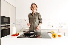 Retrato da mulher de sorriso positiva que cozinha o café da manhã saudável dentro Imagens de Stock