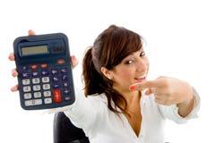 Retrato da mulher de sorriso que aponta na calculadora Fotos de Stock Royalty Free