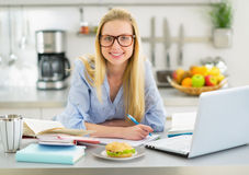 Retrato da mulher de sorriso que estuda na cozinha Foto de Stock