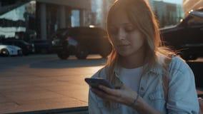 Retrato da mulher de sorriso que usa o reconhecimento de voz do smartphone Menina caucasiano nova que anda com fones de ouvido e  video estoque