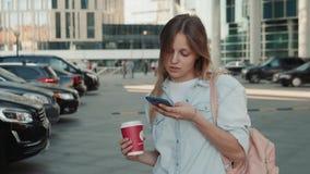 Retrato da mulher de sorriso que usa o reconhecimento de voz do smartphone Menina caucasiano nova que anda com fones de ouvido e  filme