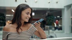 Retrato da mulher de sorriso que usa o reconhecimento de voz do smartphone Menina caucasiano nova no terminal de aeroporto com ba filme
