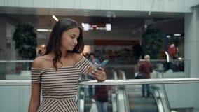 Retrato da mulher de sorriso que usa o reconhecimento de voz do smartphone Menina caucasiano nova no terminal de aeroporto com ba vídeos de arquivo