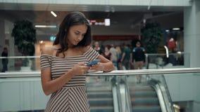 Retrato da mulher de sorriso que usa o reconhecimento de voz do smartphone Menina caucasiano nova no terminal de aeroporto com ba video estoque
