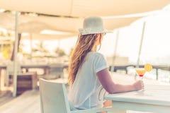 Retrato da mulher despreocupada bonita que aprecia a luz do sol e que bebe o cocktail na praia Conceito do fundo da praia do verã Imagem de Stock Royalty Free