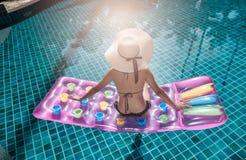 Retrato da mulher do beautifu que relaxa no biquini e no chapéu grande no swi Foto de Stock Royalty Free