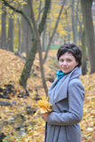 Retrato da mulher dos anos médios com as folhas de bordo amarelas nas mãos Imagem de Stock Royalty Free