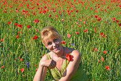 Retrato da mulher dos anos médios com papoila vermelha em uma mão Fotos de Stock