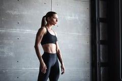 Retrato da mulher dos esportes que veste o sportswear preto no fundo escuro da parede foto de stock