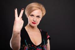 Retrato da mulher elegante fresca que mostra o número dois Imagem de Stock