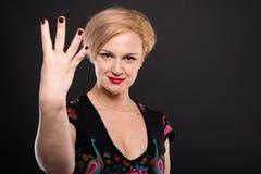 Retrato da mulher elegante fresca que mostra o número quatro Fotografia de Stock