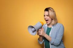 Retrato da mulher emocional que usa o megafone no fundo da cor imagens de stock royalty free