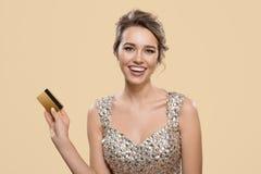 Retrato da mulher encantador feliz que guarda o cartão de banco plástico do ouro foto de stock
