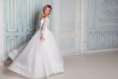Retrato da mulher encantador no vestido de casamento Dança nas paredes do fundo com moldes clássicos fotografia de stock
