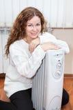 Retrato da mulher encaracolado de cabelos compridos perto do calefator de óleo imagens de stock royalty free