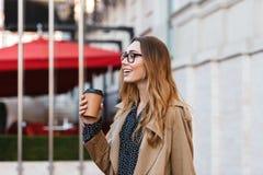 Retrato da mulher europeia que bebe o café afastado ao andar através da rua da cidade fotos de stock royalty free